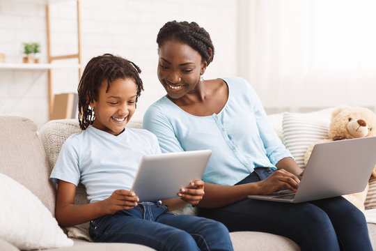 Afro mom and daughter doing school homework on sofa