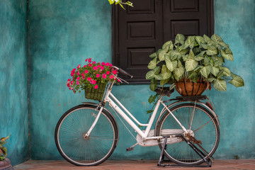 Poster de jardin Velo White vintage bike with basket full of flowers next to an old building in Danang, Vietnam
