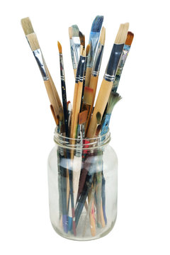 Various professional paint brushes in the transparent jar