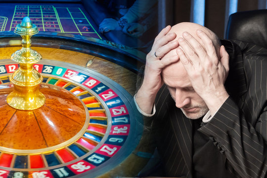 Depressed person and a view of the casino. The man clutched his head against the background of the roulette wheel. Losing at the casino. Lose money at the casino. Gambling. Cash game.