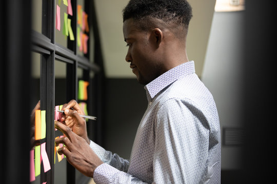 Focused African American businessman writing tasks or ideas on colorful stickers on glass wall, employee, developer planning project, organizing work, making notes on sticky papers in office