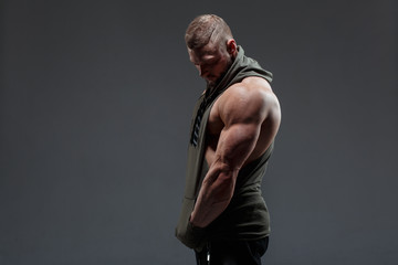 Athletic white man shows muscles side view against a dark background. Fototapete