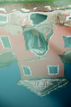 The characteristic colored houses of Burano (Venice) reflected on the water of a canal