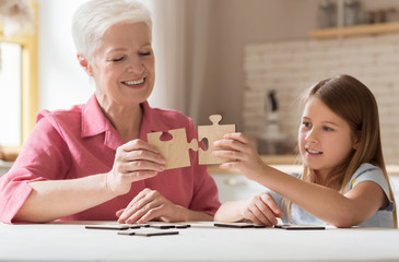 Lovely girl and her grandma solving jigsaw puzzle together at home