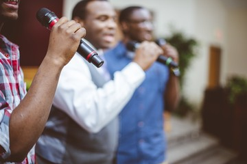Group of African-American friends singing with microphones at the church Fotobehang