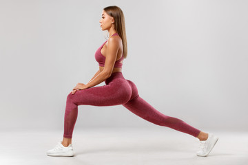 Fitness woman doing lunges exercises for leg muscle workout training. Active girl doing front forward one leg step lunge exercise, on the gray background