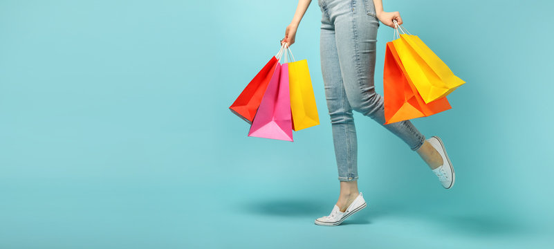 Beautiful young woman and shopping bags on blue background