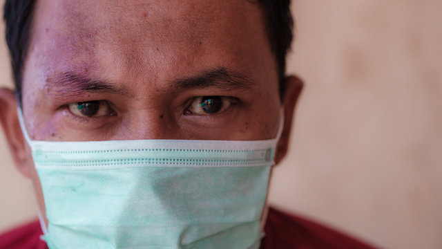 Indonesian man wearing a medical face mask to anticipate the spread of diseases outbreak caused by viruses, such as coronavirus or covid-19 and avian influenza, which become a world pandemic.