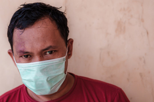Indonesian man wears medical face mask to prevent himself from diseases outbreak caused by viruses, such as coronavirus or covid-19 outbreak, which have become a global pandemic in 2020.