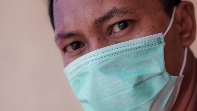 Asian man wearing a medical face mask to anticipate the spread of diseases caused by viruses, such as coronavirus or covid-19 and avian influenza, which become a world pandemic.