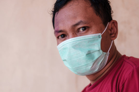 Asian man wearing a medical face mask, suitable to illustrate how to prevent every people from attack deadly diseases outbreak like coronavirus or covid-19, which become a world pandemic.