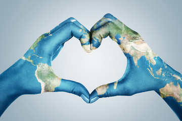 Female hands, painted in the world map,  forming heart shape isolated on blue background Fotomurales
