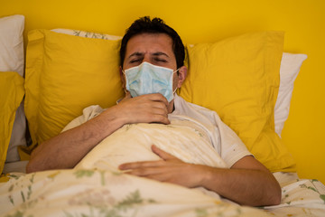 The Face of Sick caucasian Man Wearing Face Mask feeling sick headache and cough because of Coronavirus Covid-19 on the sofa in quarantine