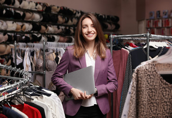 Young business owner with laptop in boutique