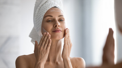 Closeup head shot pleasant beautiful woman applying moisturizing creme on face after shower. Smiling young pretty lady wrapped in towel smoothing perfecting skin, daily morning routine concept. Wall mural