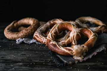 German Bread Pretzel and Bagel Breakfast on a wooden table. Black Background Fotobehang