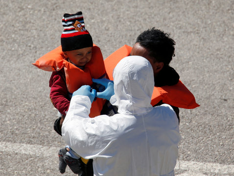 A police officer in protective clothing against possible coronavirus infection removes a life jacket from a child migrant after rescued migrants arrived on a military ship in Senglea