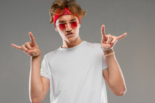 handsome cool stylish guy in white t-shirt, glasses and bandana isolated on gray background
