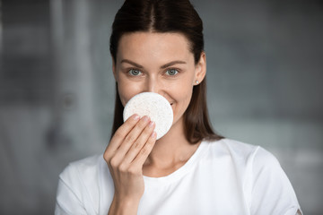 Pretty brunette woman cleansing nose with sponge, looking at camera, head shot close up portrait....