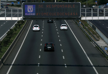 A traffic light signal advising people to be responsable and stay home is seen at M-30 ring road in Madrid