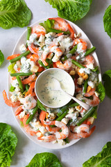 A platter of prawns and green bean salad with dill dressing.