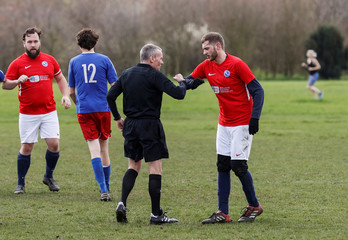 A player and referee avoid hand shakes as they play park football at Hackney Marshes in London