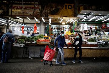 People wearing masks shop at a food market in Tel Aviv