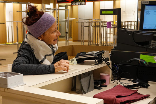 Caucasian baby boomer woman holding money stands at cashier's counter by a computer and credit card machine making a purchase