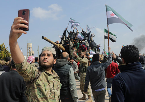 A Turkey-backed Syrian rebel fighter takes a picture with a mobile phone during a protest against the agreement on joint Russian and Turkish patrols, at M4 highway in Idlib province