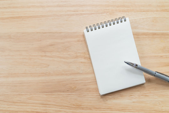 Top view of blank notebook with pen and natural light on wooden table.