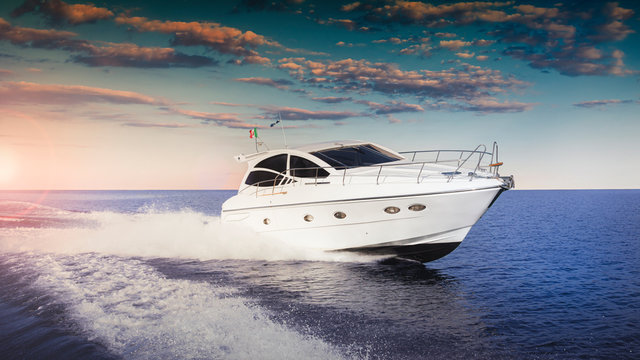 Luxurious motor boat sailing the sea at sunset
