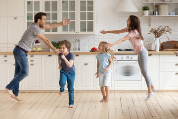 Fotorolgordijn Dance School Overjoyed young family with small kids entertain in modern spacious kitchen dancing together, happy playful parents have fun with little preschooler children engaged in funny activity at home