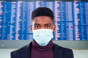 young african american business man protect his healthy with medical mask a airport time table terminal background