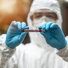 COVID-19, Corona Virus epidemic disease with doctor in PPE Personal Protective Equipment holding blood test tube