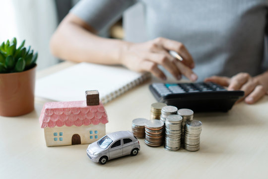 Close up hand using calculator, stack of coins, toy house and car on table, saving for future, manage to success, business and finance concept.