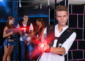 Positive young man with  laser pistol and playing laser tag with