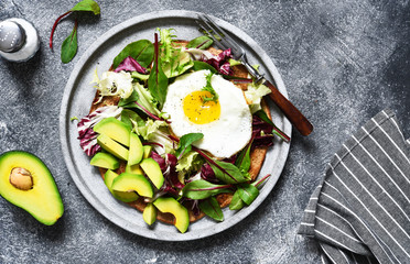 Classic breakfast - fried eggs, salad with avocado and bread toast on a concrete background.