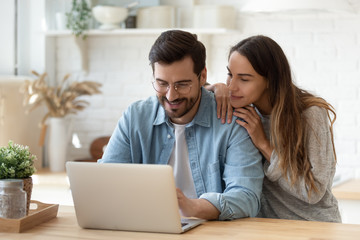 Happy young man and woman hugging, using laptop together, looking at screen, loving couple shopping...