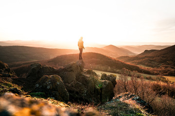 Zelfklevend Fotobehang Diepbruine Adventures man the background of mountain peaks. Man hiking in mountains. Happy traveler standing on top of a mountain and enjoying sunset view