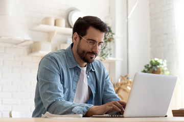 Focused young man wearing glasses using laptop, typing on keyboard, writing email or message,...