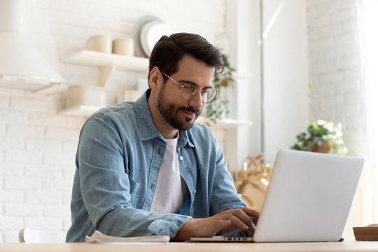 Focused young man wearing glasses using laptop, typing on keyboard, writing email or message, chatting, shopping, successful freelancer working online on computer, sitting in modern kitchen