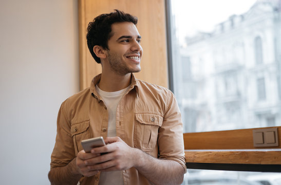 Successful Indian man using smart phone with mobile app for ordering food online on website. Happy asian guy holding cellphone, chatting, receive text message, booking tickets, looking at window