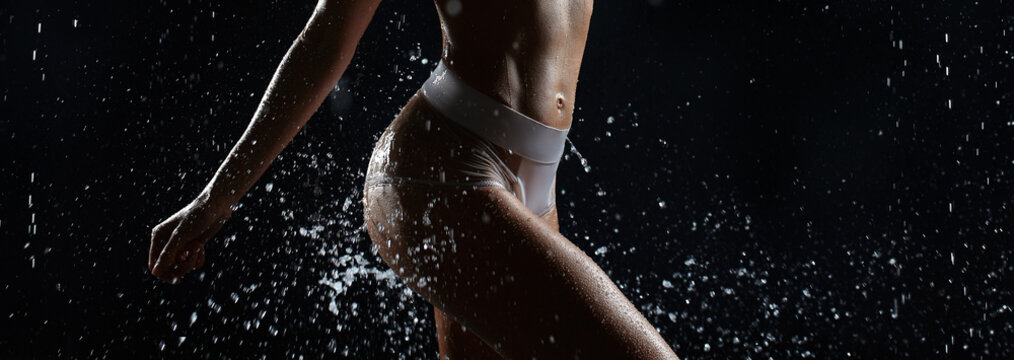 Beautiful young girl in sportswear poses in aqua studio. Drops of water spread about her fitness body. The perfect figure on the background of water splashes
