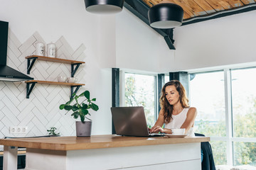 Woman is sitting at the kitchen table with laptop