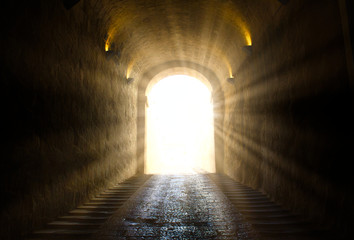 A bright yellow glowing light breaking through at the end of a dark tunnel Fotobehang