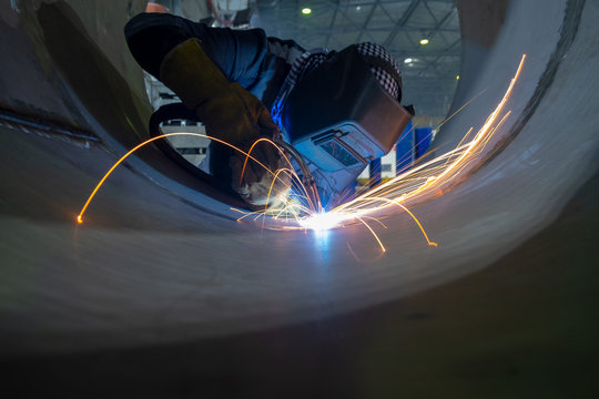 Welder performs welding work semi-automatic electric arc welding. Stainless steel pipe welding. Pipe production.