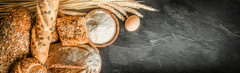 Spoed Fotobehang Bakkerij Bread with wheat and bowl of flour on dark board, White bakery food concept panorama or wide banner photo.