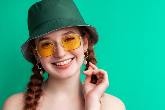 Happy smiling fashionable woman wearing yellow sunglasses, trendy green bucket hat. Close up portrait. Copy, empty space for text