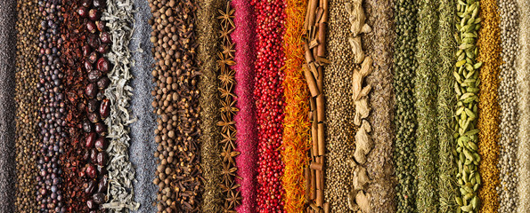 Fototapete - Spices scattered on the table, background for design. Colorful condiments as decoration of packing with food.