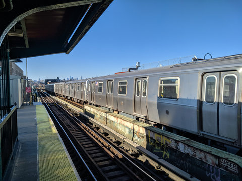 Train at platform in long Island, New York, Queens, with the skyline in the background in a sunny clear day